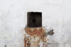 Groot zwart vierkant gat bij de oude witte steenachtige muur met een roest Stock Foto's