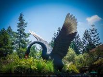 Groot zwart zwaanstandbeeld op groen bos en gras met blauwe hemel royalty-vrije stock foto