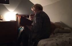 Grootmoeder die aan kleinkind leest stock foto's