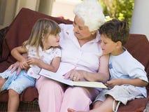 Grootmoeder die aan kleinkinderen leest Stock Foto