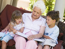 Grootmoeder die aan kleinkinderen leest Stock Afbeeldingen