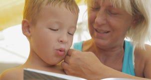 Grootmoeder die een boek lezen aan kleinzoon stock videobeelden