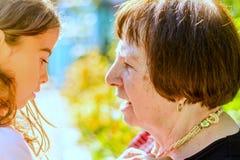 Grootmoeder die een gesprek met haar Kleindochter hebben Royalty-vrije Stock Foto's