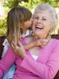 Grootmoeder die een kus van kleindochter krijgt stock foto's