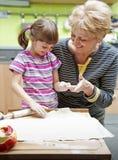 Grootmoeder die haar kleindochter het koken onderwijst Royalty-vrije Stock Foto