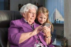 Grootmoeder die haar kleinkind iets tonen grappig op haar smartp stock afbeelding