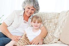 Grootmoeder die haar meisje helpt stock foto