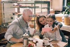 Grootmoeder die haar roze smartphone houden die foto's tonen aan kleindochter stock fotografie