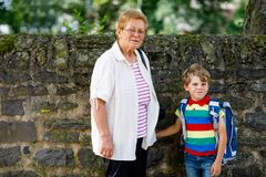 Grootmoeder die kind, jong geitjejongen aan school op zijn eerste dag nemen stock foto