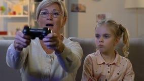 Grootmoeder die kind negeren terwijl het spelen van videospelletje met console, verslaving stock videobeelden