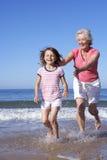 Grootmoeder die Kleindochter langs Strand achtervolgen Stock Foto's