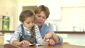 Grootmoeder die Kleindochter met thuis het Lezen helpen stock videobeelden