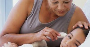 Grootmoeder die lichaamstemperatuur van zieke kleindochter in bedruimte 4k controleren stock footage