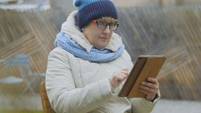 Grootmoeder die met tablet in openlucht ontspannen stock footage