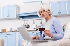 Grootmoeder die online opslag bezoeken stock afbeelding