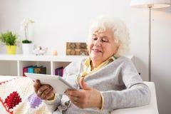 Grootmoeder die tabletcomputer in haar woonkamer met behulp van royalty-vrije stock foto's