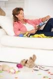 Grootmoeder die van een rust op bank geniet stock afbeeldingen