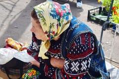 Grootmoeder die zit en wacht op koper hebben de gebogen stock foto