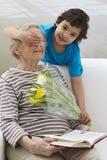 Grootmoeder door haar kleinzoon wordt verrast die bloemen aanbieden die Stock Afbeelding