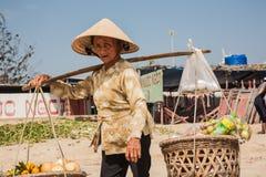 Grootmoeder, een verkoopster van vruchten en groenten op het strand Royalty-vrije Stock Afbeeldingen