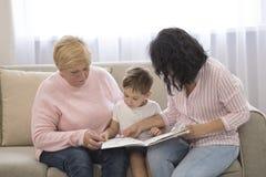 Grootmoeder en dochter die een verhaal lezen aan haar kleinzoon De Vrije tijd van de familielezing stock afbeeldingen