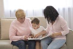 Grootmoeder en dochter die een verhaal lezen aan haar kleinzoon De Vrije tijd van de familielezing royalty-vrije stock foto's