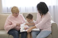 Grootmoeder en dochter die een verhaal lezen aan haar kleinzoon De Vrije tijd van de familielezing stock foto