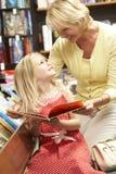 Grootmoeder en grandaughter in boekhandel Stock Fotografie