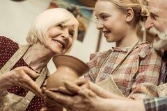 Grootmoeder en grootvader met de kleivaas van de kleindochterholding royalty-vrije stock afbeeldingen