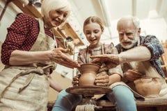 Grootmoeder en grootvader met kleindochter die aardewerk maken royalty-vrije stock afbeeldingen
