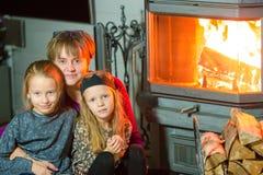 Grootmoeder en haar twee kleine kleindochters die door een open haard in hun familiehuis zitten op Kerstmisvooravond royalty-vrije stock foto's