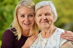 Grootmoeder en kleindochter De jonge vrouw neemt zorgvuldig zorg stock fotografie