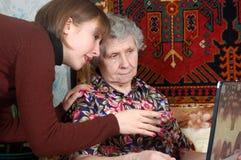 Grootmoeder en kleindochter die aan laptop kijken Royalty-vrije Stock Afbeeldingen