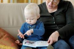 Grootmoeder en kleindochter die een boek lezen Stock Afbeeldingen