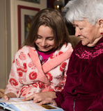 Grootmoeder en kleindochter die een boek lezen stock foto's