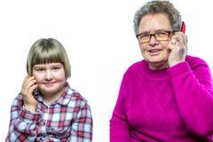 Grootmoeder en kleindochter die met mobiele telefoon telefoneren Royalty-vrije Stock Afbeeldingen