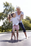 Grootmoeder en Kleindochter die op Trampoline stuiteren royalty-vrije stock afbeelding