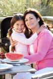 Grootmoeder en Kleindochter die Openluchtbarbecue hebben Royalty-vrije Stock Foto