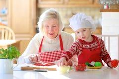 Grootmoeder en kleindochter die pizza voorbereiden Stock Foto's