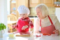Grootmoeder en kleindochter die pizza voorbereiden Royalty-vrije Stock Foto