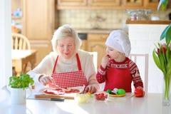 Grootmoeder en kleindochter die pizza voorbereiden Stock Afbeeldingen