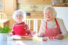 Grootmoeder en kleindochter die pizza voorbereiden Royalty-vrije Stock Afbeeldingen