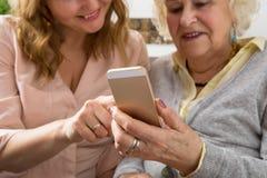 Grootmoeder en kleindochter die smartphone onderzoeken stock fotografie