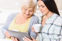 Grootmoeder en kleindochter die tablet bekijken Royalty-vrije Stock Afbeeldingen