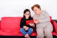 Grootmoeder en kleindochter die Tabletpc met behulp van Stock Afbeelding