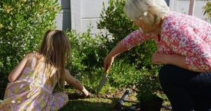 Grootmoeder en kleindochter die in tuin 4k planten stock footage