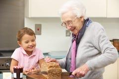 Grootmoeder en kleindochter die voedsel voorbereiden stock afbeelding