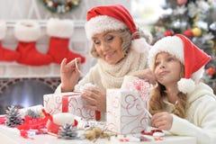 Grootmoeder en kleindochter die voor Kerstmis voorbereidingen treffen stock foto's