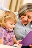 Grootmoeder en kleindochter gelezen boek samen royalty-vrije stock afbeeldingen