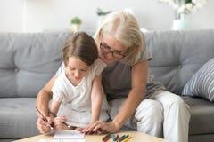 Grootmoeder en kleindochter het schilderen beeld op papier samen stock foto
